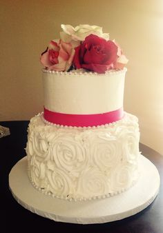 2 tier white buttercream wedding cake with buttercream rosettes and pink ribbon and pearl accents from fifth ave cakes in Bloomington, MN