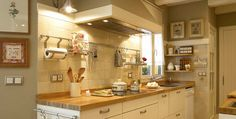 Modern slab cabinets can work in a country kitchen. Handmade tiles in sunny yellow, stainless wall rail holds paper towels, cooking tools, and cookbook. Butcherblock counter. Induction cooktop. Drainboard stainless sink. Roll-in/roll out dishwasher (not built in). Large hood with lights. | DEULONDER