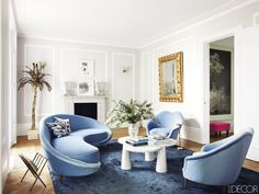 Modern french blue sofa and chairs in a white living room with gold accents