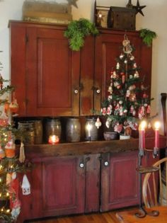 Prim Christmas...old red cupboard with crocks & decorated trees.