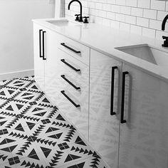 Black and white encaustic tile, matte black fixtures, white vanity.