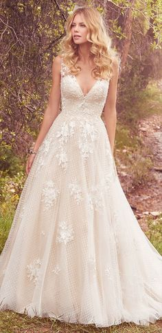 This vintage-inspired ballgown features lace appliqués over whimsical layers of dotted tulle and Chic organza. Featuring a V-neckline, illusion straps accented with lace appliqués, and square back. Swarovski crystals and beading add shimmer and ethereal texture.