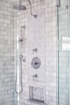 Multiple polished nickel shower heads are fitted in a seamless glass shower boasting marble subway surround tiles fixed framing marble herringbone accent tiles and a marble herringbone tiled niche.