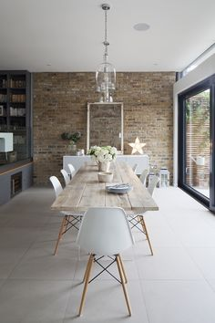 Broadgates Road - Granit Architects. Dining area with glass pendant lights above. Eames chairs and reclaimed timber table with perspex stand. Exposed brick wall with glass artwork on console table. Neutral tiles throughout. Sliding black framed glass doors. Clever wine fridge and storage beneath mezzanine level. Project renovation and extension in Wandsworth, South West London.