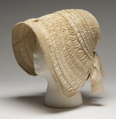 Ivory-colored shirred silk poke bonnet constructed on buckram (est.) foundation on framework of steel, baleen and wood wires; wires spaced from 1 cm to 1.5 cm apart. Bonnet has 15 cm (5-7/8 in)-wide rounded front brim with wired edge which projects beyond face, small crown at back and, attached at back, a 10.1 cm (4 in) wide self-fabric curtain to protect back of neck. Bonnet lacks ties. (8626.3) Minnesota Historical Society