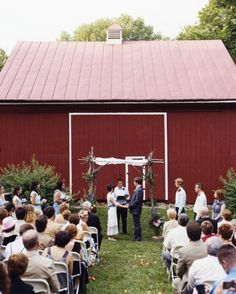 Bride and groom Amy and Leo chose to host their wedding at Amy's parents' farm, which set the rustic tone for the whole day. Here, a friend of the couple marries them under the huppa that Amy's dad built with wood cleared from the property.