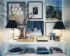 I am loving the vignette above on the console table. the black and white act as the neutrals to the (few) colors that do pop from the pictures and books. Wonderful! #pictures, #vignette, #consoles