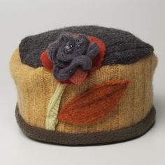 This is a ladies Rosette hat in wheat and olive recycled wool, with a floral embellishment in coordinating colors. This style hat is about 4 inches deep; not as deep as the Flower Pot hat, and work…