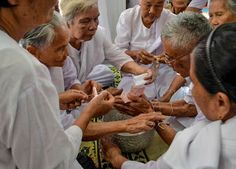 Village elders tying bracelets to wrists of local grandpa. Monk Blessed String Bracelets in Thailand (Sai Sin Sacred Thread). String blessed by monks to bring good luck and protection. Traditions and Culture in rural Thailand (Isaan) by http://potatoinrice.com/