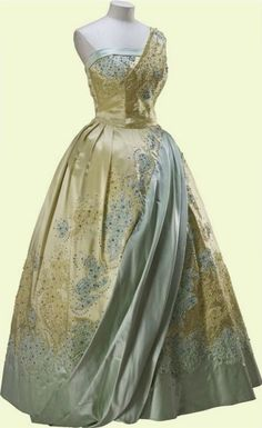 Evening Gown, Norman Hartnell: 1958, satin, lace, embroidered with sequins, diamanté and beads and has a single-shouldered bodice and a full crinoline skirt. It was worn by HRH Queen Elizabeth II to a banquet during the State Visit to the Netherlands in March 1958.
