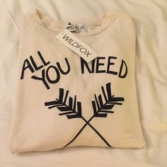 NWT WILDFOX ''ALL YOU NEED' Sweater ⚠️NEVER WORN⚠️ Super soft camel/cream colored scoop neck sweater. The writing is black and says ALL YOU NEED IS LOVE with two arrows. In perfect condition and the price is negotiable. Its got an oversized fit and could fit up to a large Wildfox Sweaters Crew & Scoop Necks