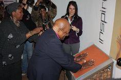 Archbishop Emeritus Desmond Tutu places his hands in the handprints of former South African president, Nelson Mandela,at Maropeng. Tutu visited Maropeng on July 31