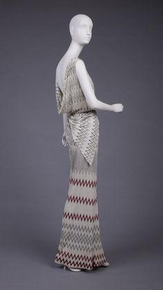 Dress, Elsa Schiaparelli: 1934, Long Knit Tricot Dress, Black/Red Zigzag Design On Off-White Groundlow V Back With Wrap Around Scarf Type Belt.