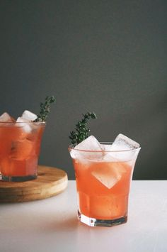 Blood Orange + Whiskey Cockails topped with sprigs of thyme. Love this warming winter cocktail recipe!