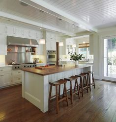 Modern cottage kitchen with glossy white beadboard ceiling and white box beams. White wood paneled center island with butcher block countertop and sawhorse counter stools. Love the chocolate wood kitchen design interior design ideas design New Kitchen, Kitchen Decor, Kitchen Ideas, Kitchen Designs, Kitchen Layout, Kitchen Photos, Long Kitchen, Kitchen White, Kitchen Rustic