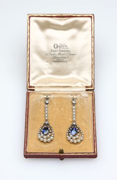 Lot# 1062 A pair of Edwardian sapphire, seed pearl and diamond ear pendants. Circa 1915, platinum, each suspending one oval-cut sapphire totaling approximately 2.50 cts, surrounded by 40 single cut and 4 old European-cut diamonds totaling approximately 0.80 ct, and 26 seed pearls, 2'' long, , est: $2500/3500 *Price Realized: $10,800.00