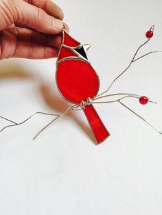 Belle suncatcher cardinal rouge fait avec un verre transparent semi rouge vif, il est assis sur une branche de fil ornée de verre rouge « baies » les branches fan en les éloignant de la fenêtre donnant à cette pièce un effet de 3 dimensions. Une aspiration est incluse. Fait avec soin en utilisant la méthode de la feuille de cuivre traditionnel. Le cardinal lui-même mesure 5.25 x 2 » et la pièce entière avec branches 8,5 x 8 . Cet article est fabriqué sur commande et généralement expédié…
