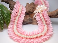 Hundreds of pink petals were hand cut from ribbon and stitched into place. The lei easily slips over a persons head. Ive also added an accent bow