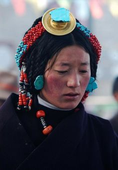 Female pilgrim from Derge in western Kham. Derge and Chamdo are the only parts of Kham inside the CCP designated 'Tibetan Autonomous Region' The large amulet with turqoise chunk, and the coral and turqoise bands of beads across the crown of her head are ornaments that are specific to women of Derge.