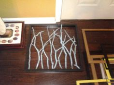 Branches, spray paint, a deep frame, and a hot glue gun... We put the sticks we'd already spray painted but didn't use here into a glass vase and set it on the coffee table to bring it all together.