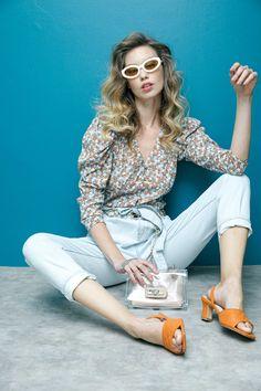 Camisa floreada y sandalias naranjas MAP, jeans de mezclilla con cinturón Petite Studio, clutch transparente  Steve Madden y lentes de sol ovalados Le Specs.