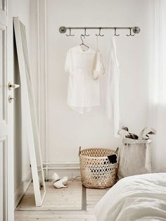 Kledingrek in witte slaapkamer