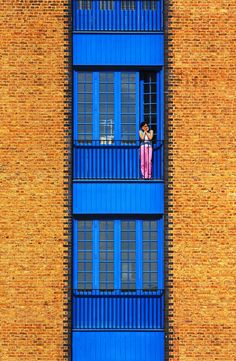 London...luv the contrast between the golden bricks and the bright blue paint with a touch of hot pink...