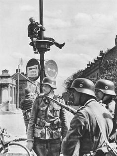 "An advanced element of the SS ""Totenkopf"" Division rearranges road signs in a French city in order to accelerate the movement of German troops rolling on the offensive, summer 1940."