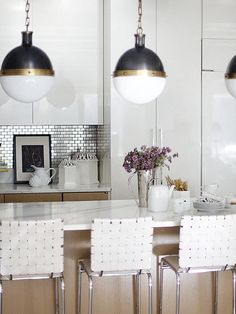 Stainless steel tile backsplash in a white kitchen with metallic accents