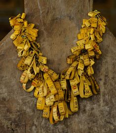 """Take Measure Necklace in vintage, cloth tape measures, tiny glass vial with fortune enclosed, enameled metal rivets, brass jump rings, chain, and clasp. 21"""" in length. Exhibit: Signs of Life 2010   Chris Giffin"""