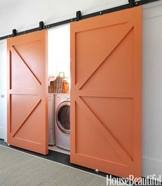 """Barn doors painted the same bold orange pack a punch in the laundry area. """"The doors to the laundry room could have been a lost opportunity—just another pair of white doors,"""" says Berman. """"But we felt they shouldn't be an afterthought.  Painting them orange made them very visible and special. They read as art."""" Jonny Valiant  - HouseBeautiful.com"""
