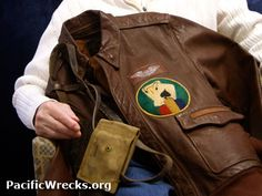 """WWII veteran fighter pilot, John Lolos holding his leather flight jacket with """"Black Jack"""" insignia with pistol holster."""