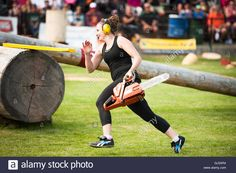 Download this stock image: A woman competitor in the open open obstacle bucking event .  The Squamish Loggers Day Loggers Sports event.  Female logger with a chainsaw. - GJ5XR4 from Alamy's library of millions of high resolution stock photos, illustrations and vectors.