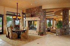 Large luxury home with small designated dining area in open living area partitioned by large stone fireplace
