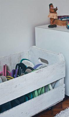Pintura branca e rodinhas transformaram o caixote de feira em abrigo para a coleção de chinelos.