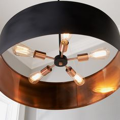 This sleek modern chandelier surrounds a five light cluster with a thin metal drum shade. The Matte Black shade has a metallic Copper interior and seems to float around the fixture due to subtle wire suspensions. Copper Light Fixture, Dining Room Light Fixtures, Copper Lighting, Ceiling Fixtures, Pendant Lighting, Drum Shade Chandelier, Black Chandelier, Modern Chandelier, Ceiling Chandelier