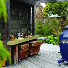 26 great ideas for decks | Create an outdoor bar | Sunset.com --- I like the rolling storage cabinets under the counter. Also, blue! :)