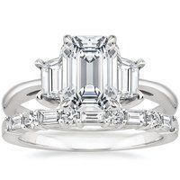 Two distinctive trapezoid-shaped diamonds sit on either side of the center gemstone in this captivating and contemporary three stone ring.