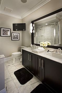 Soothing color palette and sophisticated subtly masculine style - and a flatscreen mounted where it can be viewed while at the vanity or in the tub and shower....