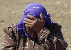 A Syrian refugee who just crossed the border into Turkey hides her face at the border in Suruc, Turkey, Sunday, Sept. 21, 2014.