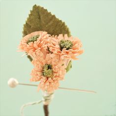 It is made from a grouping of three vintage peach/pink flowers with green centers. They have a papery texture that is frayed in a really texturally rich way.    Each has a single velvet green leaf as a backing, plus a bit of ribbon and green baker's twine at the base.