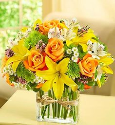 Fields of Europe™ in Rectangle Vase  At the heart of every great European city is a flourishing flower market. With gorgeous orange roses, lilies, alstroemeria and poms, this hand-arranged bouquet in a modern glass vase tied with raffia presents a contemporary spin on an old-world tradition.