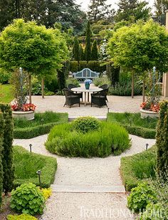 """Provençal Seating Area  At the end of an axis, a classic Lutyens bench by Barlow Tyrie in Benjamin Moore's """"Whipple Blue"""" gives a subtle Provençal feel. Blue tuteurs in pots by The Brookfield Co. are a classic embellishment. The quartet of trees growing up through the gravel are globe locusts."""
