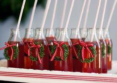 Botellitas transparentes con zumo de arándanos para ofrecer en fiesta de Navidad.