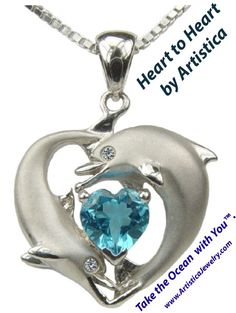"""Two curious dolphins encircle a beautiful one carat heart-shape ocean blue topaz as petite diamonds sparkle in their eyes (.015 Carat). A unique design to wear for your love of the ocean and all precious life that dwells within. Made in Platinum-Glazed Sterling Silver with genuine diamonds. Includes platinum-glaze silver adjustable box chain that can be worn at 16"""" or 18"""" in length. Artistica. Take the Ocean with You."""