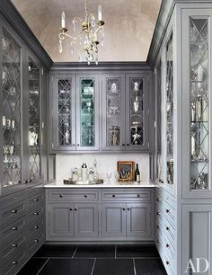 Diamond-pattern glass door fronts and a crystal chandelier lend a dressed-up look to the cabinetry in the butler's pantry.