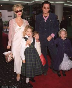 Happy family? The surviving members of INXS have alleged that Paula Yates, seen with Hutchence and her daughters in 1996, was determined to 'get' him - while Hutchence had planned to end their relationship