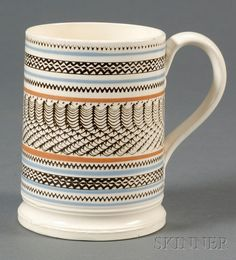Mochaware Mug with Engine-turned Design, Britain, early 19th century, pearlware mug with applied handle with leaf terminals, molded base, thin rust and blue bands flanking black slip-filled engine-turned patterned bands