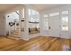 Simple yet elegant front entrance in white with wood flooring. Small built-in sofa is to the right of the front door. Stairwell is also to the right which is brightly illuminated with two stories of windows. Built In Sofa, Sweet Home, Grand Foyer, Grand Entrance, Foyer Decorating, Decorating Ideas, Elegant Homes, Nantucket, Home Improvement Projects