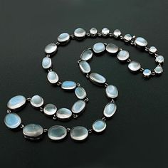 """A stunning sterling and moonstone necklace from the Victorian (ca1880) era! This flowing river of beautiful cabochon moonstones is comprised of 35 bezel and prong set stones that are round and oval in shape. Each stone is set in sterling silver and are joined together by sterling jump rings. The moonstones graduate in size and have a wonderful clear, blue color. The necklace measures 17.5"""" in length."""